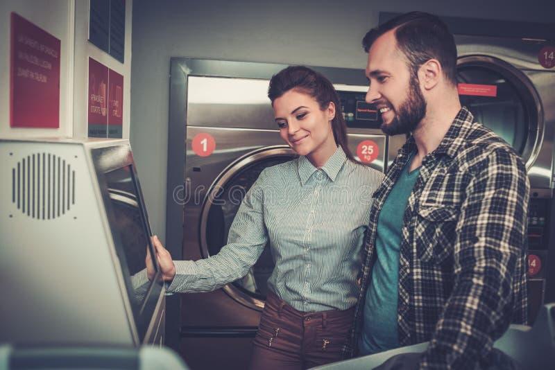 Pares alegres novos que fazem a lavanderia junto na loja da lavagem automática imagens de stock