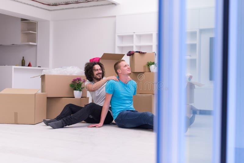 Pares alegres novos que movem-se na casa nova foto de stock royalty free