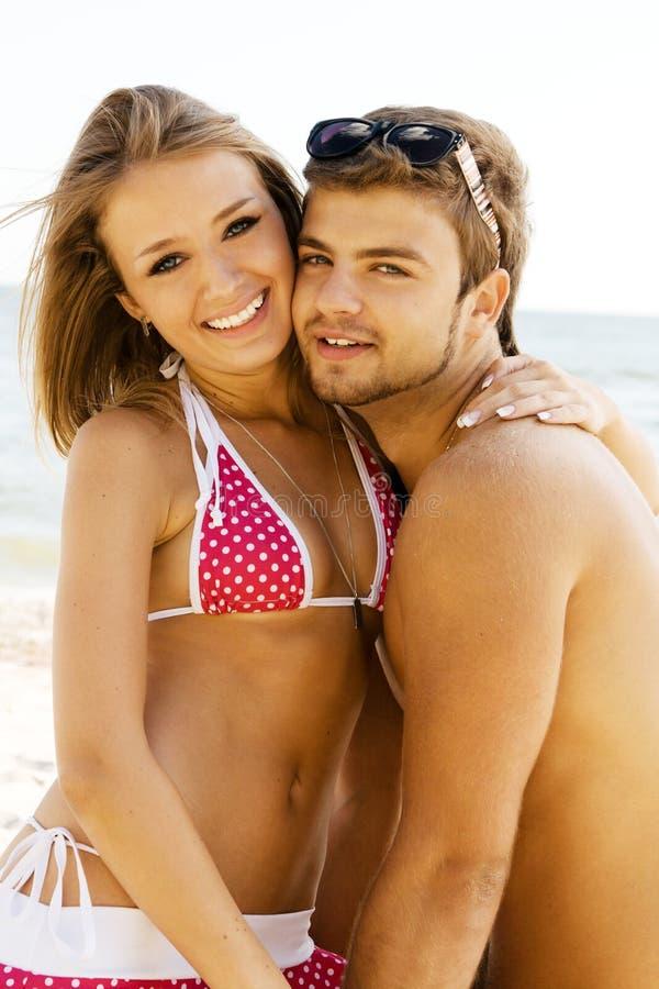 Pares alegres novos que têm o divertimento na praia fotos de stock royalty free