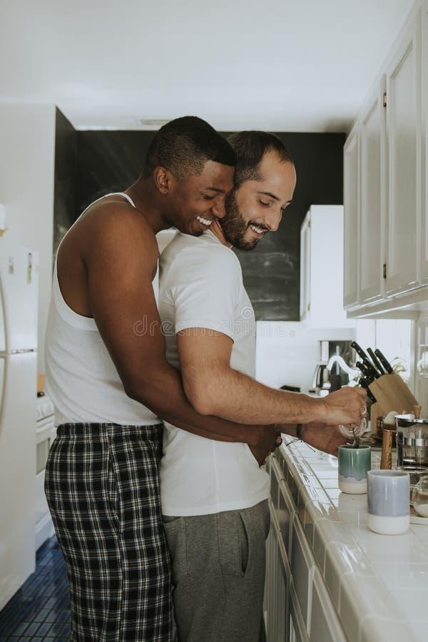 Pares alegres que abraçam na cozinha fotografia de stock