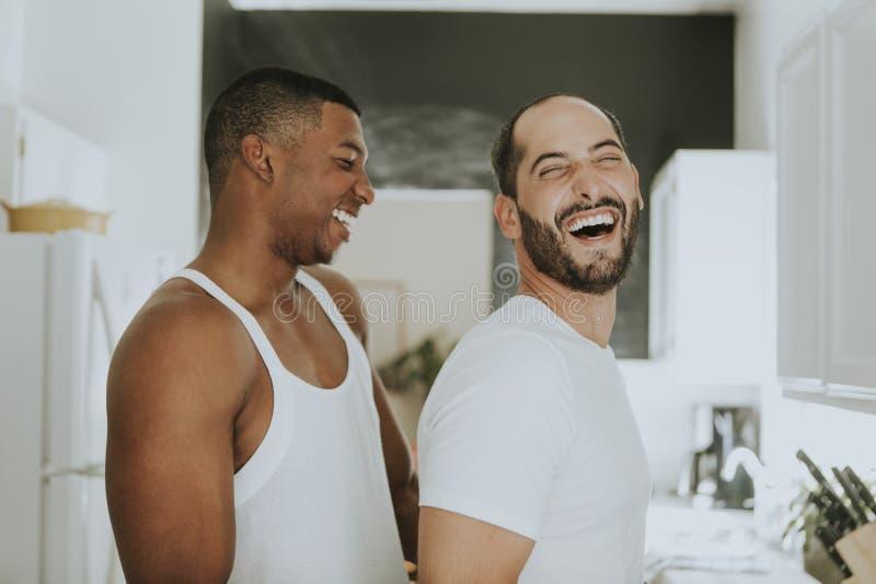 Pares alegres que abraçam na cozinha fotos de stock royalty free
