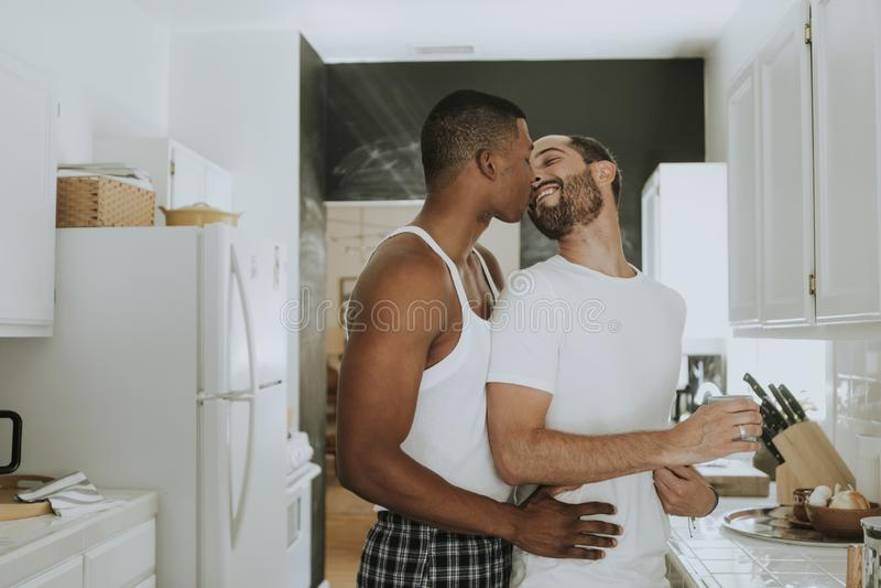 Pares alegres que abraçam na cozinha foto de stock