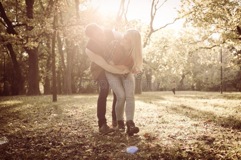 Pares alegres que abrazan en parque imagen de archivo