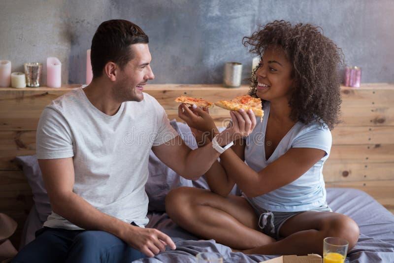 Pares alegres que alimentam-se com pizza saboroso fotos de stock