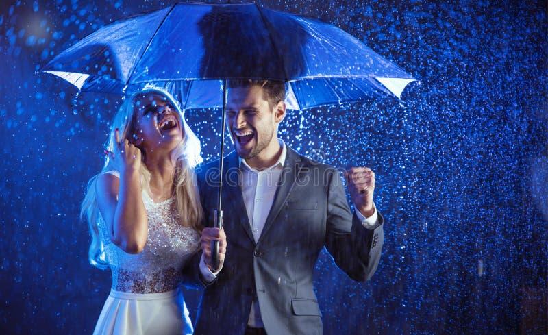 Pares alegres que apreciam a chuva do verão fotografia de stock