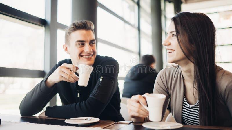 Pares alegres que apreciam o café junto no café moderno Bebida quente bebendo da cafeína em uma ruptura com sócio comercial imagem de stock