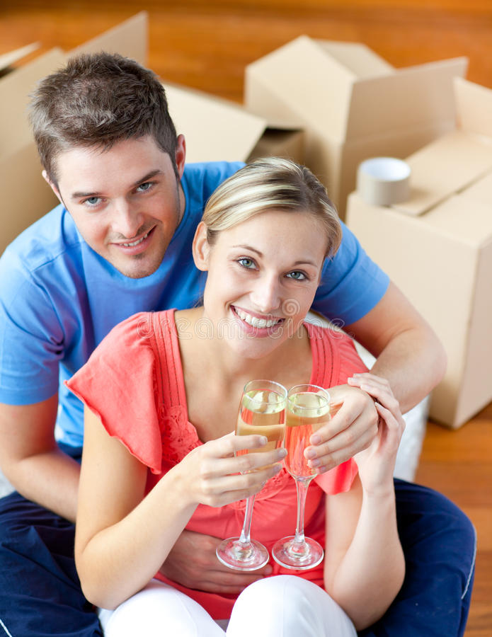 Pares alegres que comemoram a casa com champanhe foto de stock royalty free