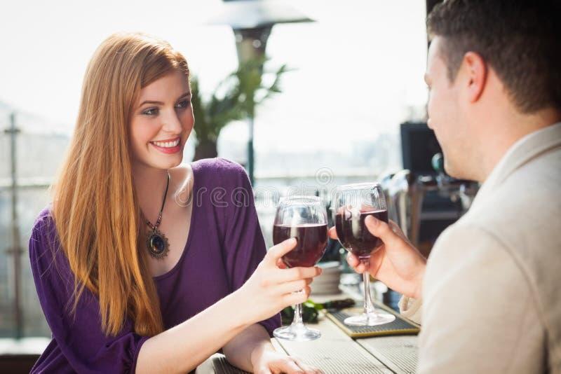Pares alegres que comen el vidrio de vino junto fotografía de archivo