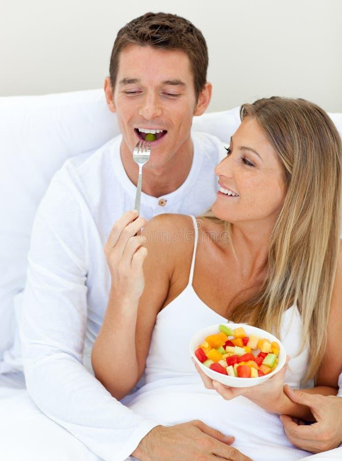 Pares alegres que comen la fruta que miente en su cama foto de archivo libre de regalías
