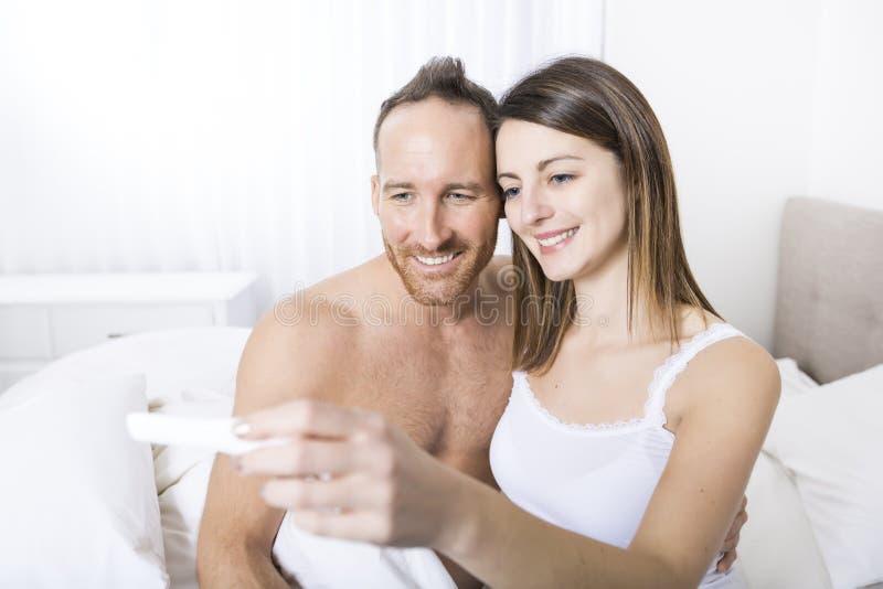 Pares alegres que encontram resultados de um teste de gravidez que senta-se na cama fotografia de stock