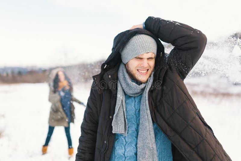 Pares alegres que jogam bolas de neve em um campo nevado no inverno imagem de stock royalty free