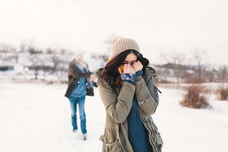 Pares alegres que jogam bolas de neve em um campo nevado no inverno imagens de stock royalty free