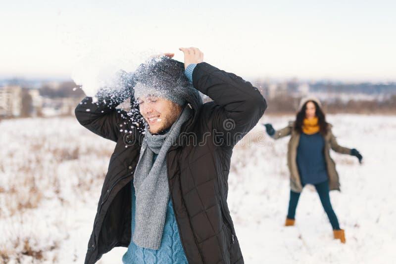 Pares alegres que jogam bolas de neve em um campo nevado no inverno foto de stock