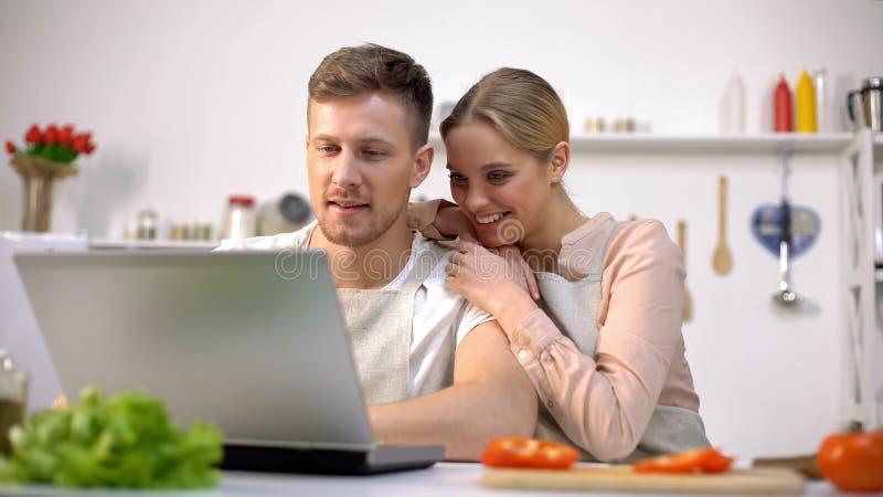 Pares alegres que miran cocinando tutoriales en línea, preparación romántica de la cena imágenes de archivo libres de regalías