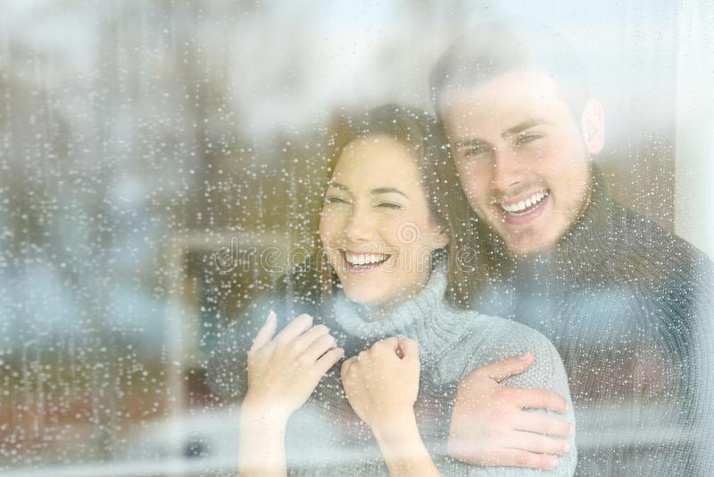 Pares alegres que miran a través de una ventana al día lluvioso foto de archivo