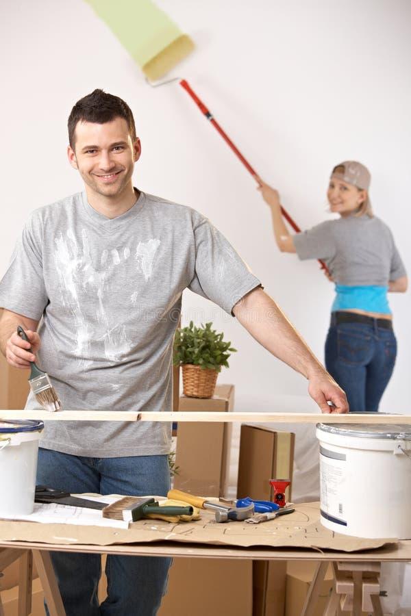 Pares alegres que pintam sua HOME foto de stock royalty free