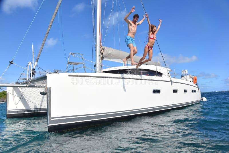 Pares alegres que saltam do barco de navigação ao mar fotografia de stock royalty free