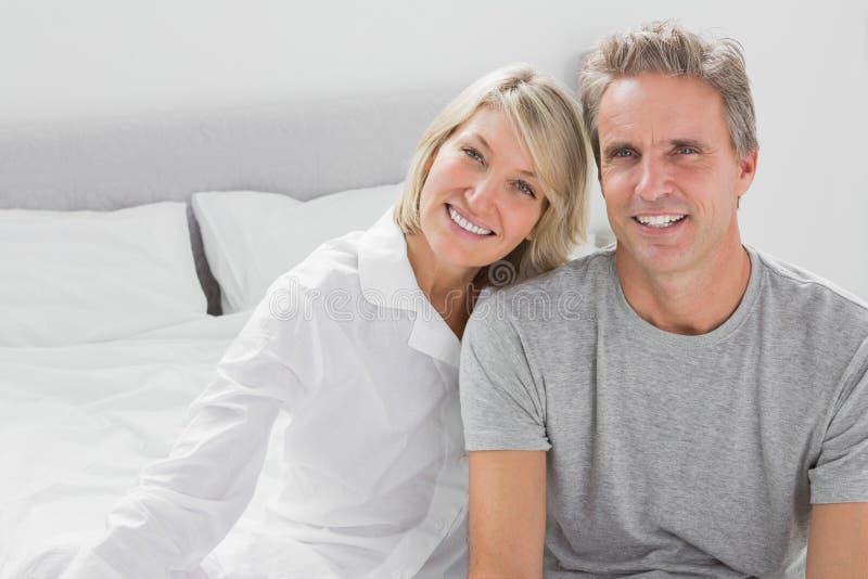 Pares alegres que sentam-se na cama imagens de stock