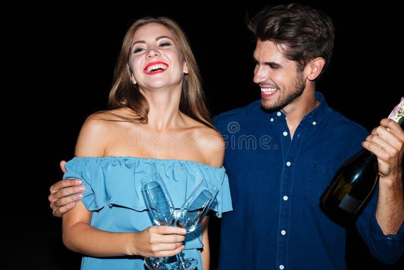 Pares alegres que sostienen los vidrios y la botella de champán en la noche fotografía de archivo libre de regalías