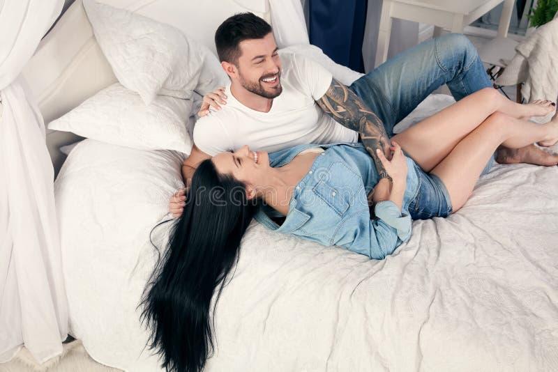 Pares alegres 30s que abraçam junto ao encontrar-se na cama em casa ou no apartamento do hotel fotos de stock royalty free