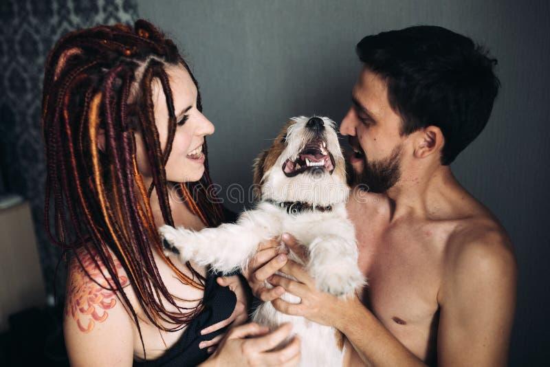 Pares alegres y felices y el perro, sonriendo y mostrando tongu imagen de archivo libre de regalías