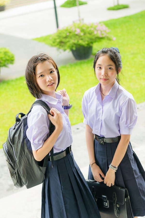 Pares altos tailandeses asiáticos bonitos do estudante das estudantes na farda da escola fotografia de stock