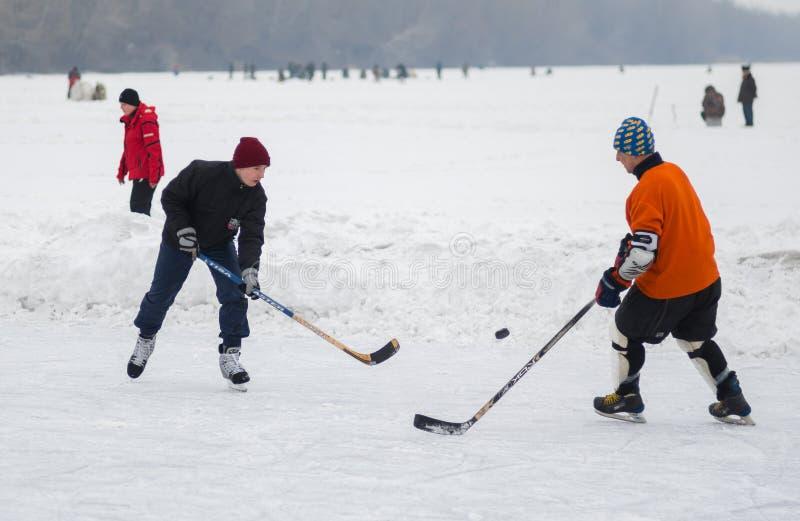 Pares amadores novos e homens maduros que jogam o hóquei em um rio congelado Dnepr em Ucrânia fotografia de stock royalty free