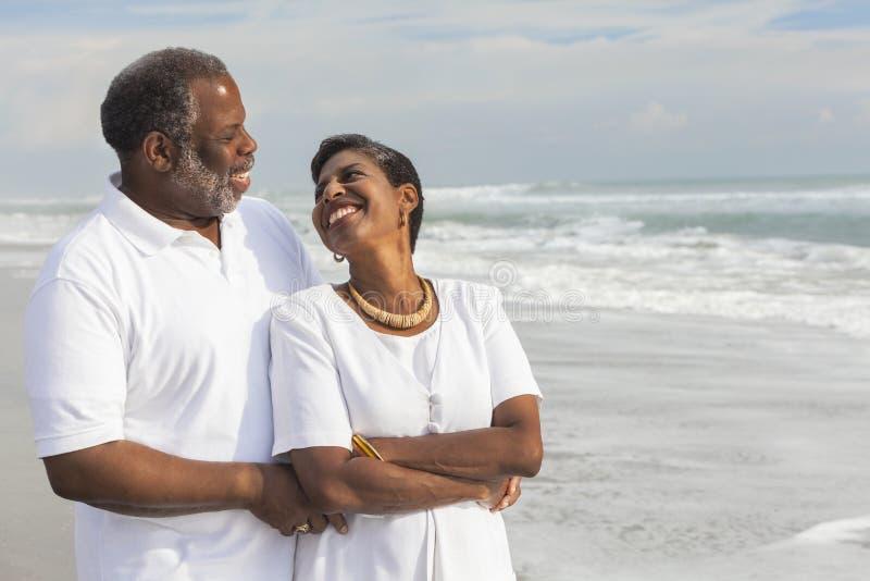 Pares americanos africanos superiores felizes na praia fotos de stock royalty free