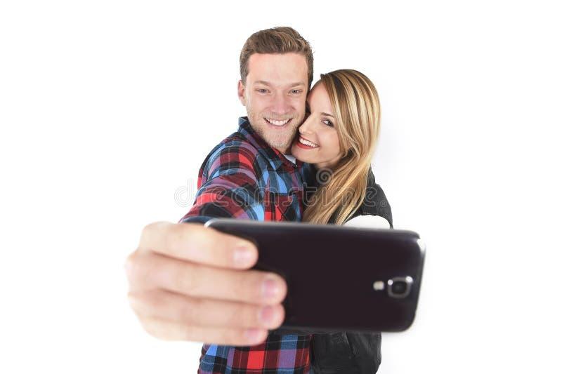 Pares americanos bonitos novos no amor que toma a foto romântica do selfie do autorretrato junto com o telefone celular imagem de stock royalty free