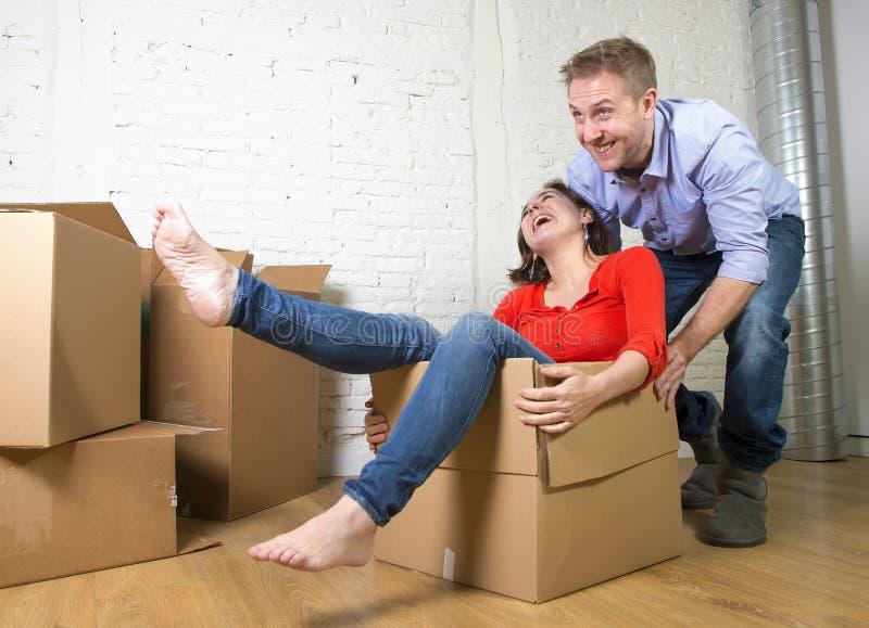 Pares americanos felices que desempaquetan la mudanza en la nueva casa que juega con las cajas de cartón desempaquetadas foto de archivo
