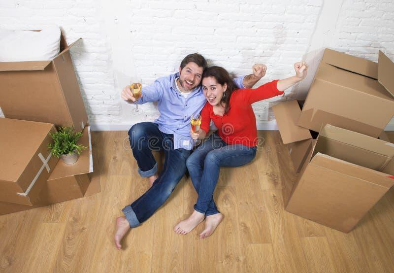 Pares americanos felices que se sientan en el piso que desempaqueta junta la celebración de la mudanza al plano o al apartamento  foto de archivo libre de regalías