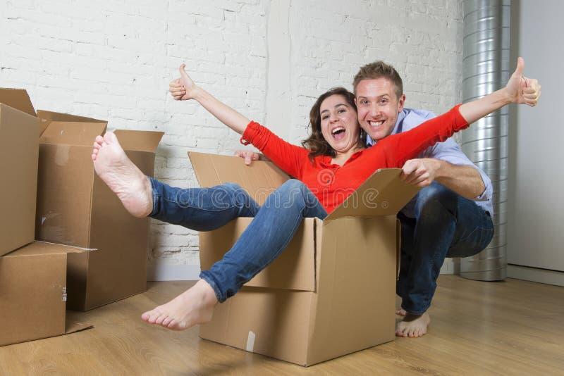 Pares americanos felizes que desembalam mover-se na casa nova que joga com as caixas de cartão desembaladas foto de stock