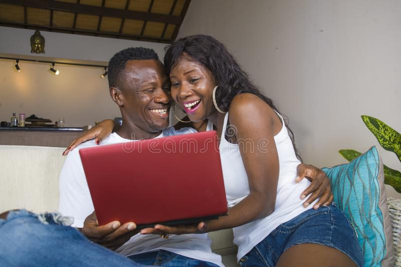 Pares americanos novos do africano negro feliz e bonito no amor que aprecia no sofá do sofá da sala de visitas com riso do laptop fotos de stock
