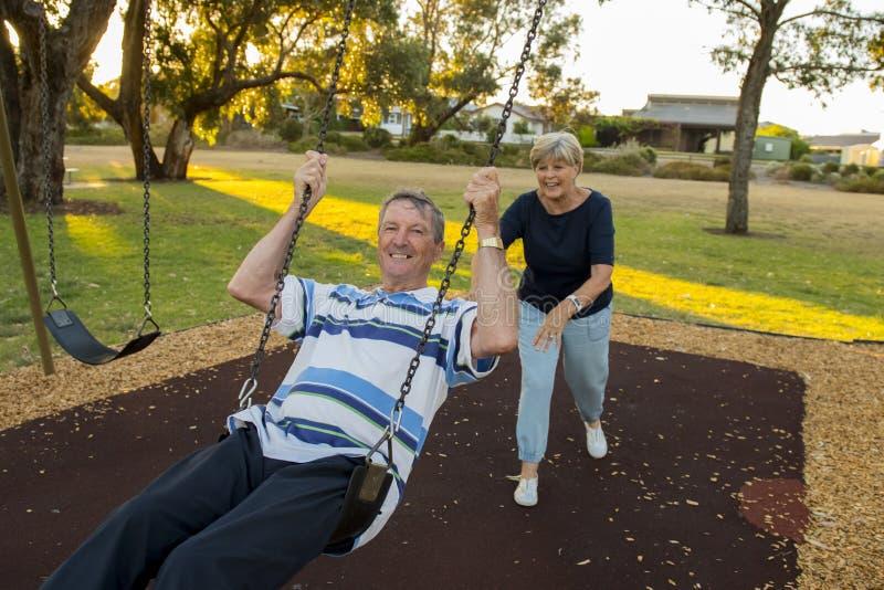 Pares americanos superiores felizes ao redor 70 anos de apreciação velha no parque do balanço com a esposa que empurra o marido q fotografia de stock