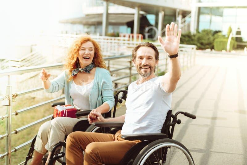 Pares amistosos en las sillas de ruedas que acogen con satisfacción a un extranjero imagen de archivo