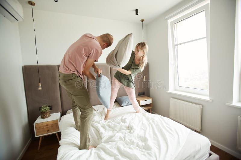 Pares amorosos jovenes despreocupados con las almohadas que se divierten imagen de archivo libre de regalías