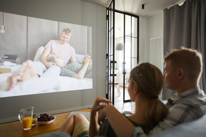 Pares amorosos jovenes que miran su video casero imagen de archivo