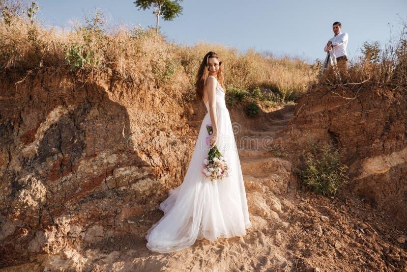 pares Apenas-casados que caminan en la playa foto de archivo libre de regalías