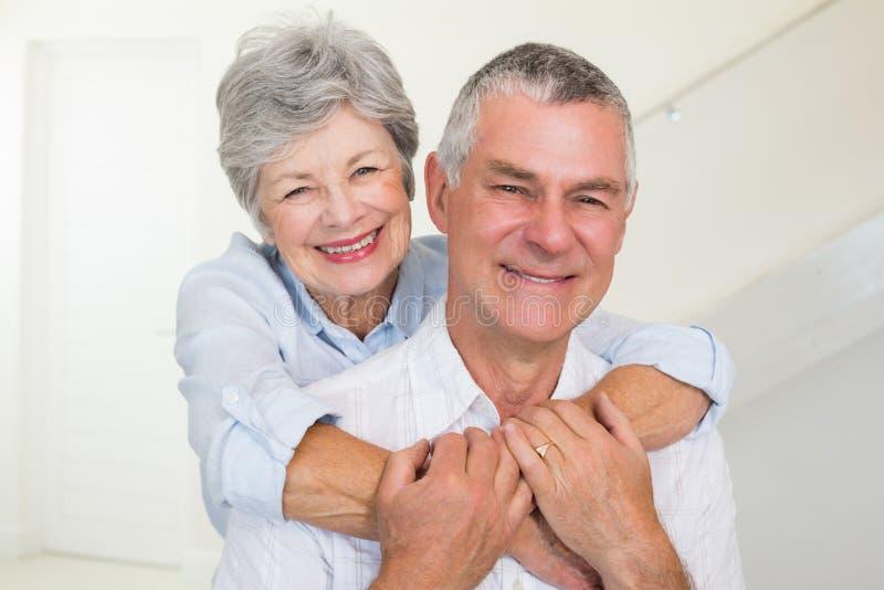 Pares aposentados afetuosos que sorriem na câmera foto de stock