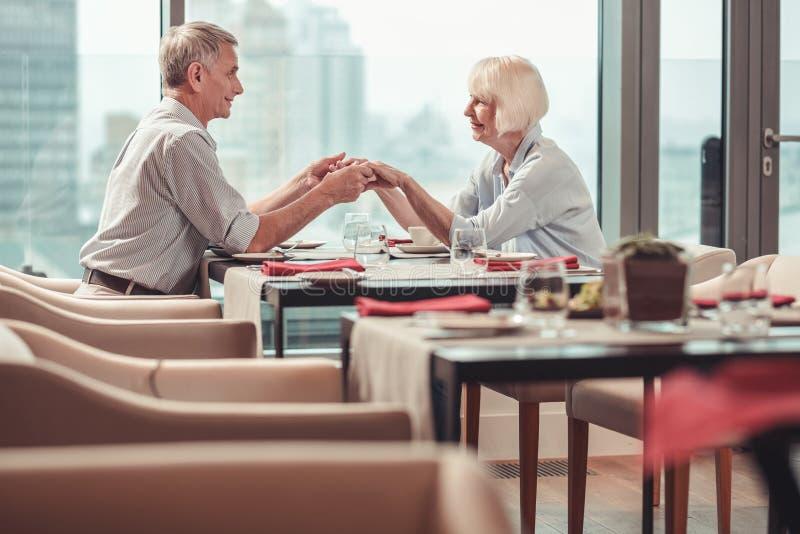Pares aposentados exuberantes que têm o almoço em um restaurante imagem de stock royalty free
