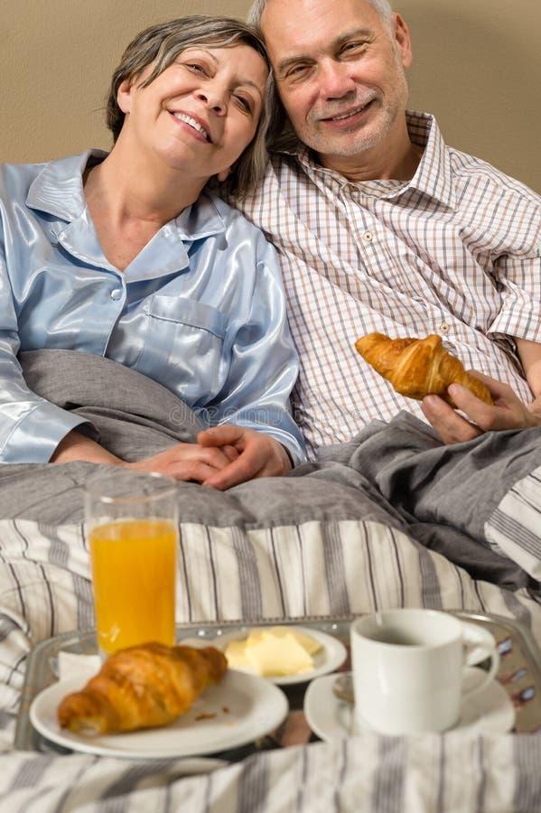 Pares aposentados felizes que comem o café da manhã do croissant imagens de stock