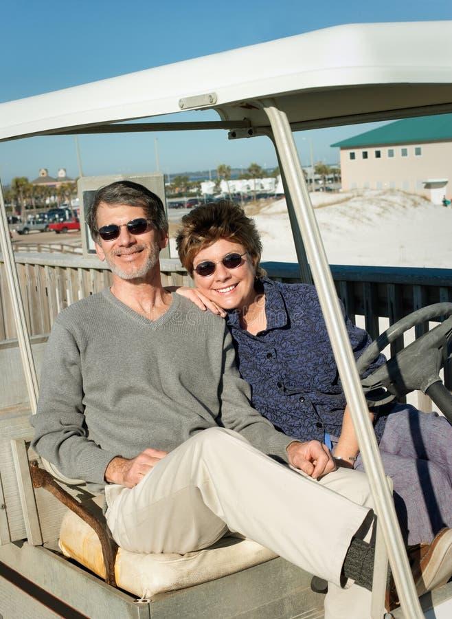 Pares aposentados no carro de golfe velho na praia imagens de stock royalty free