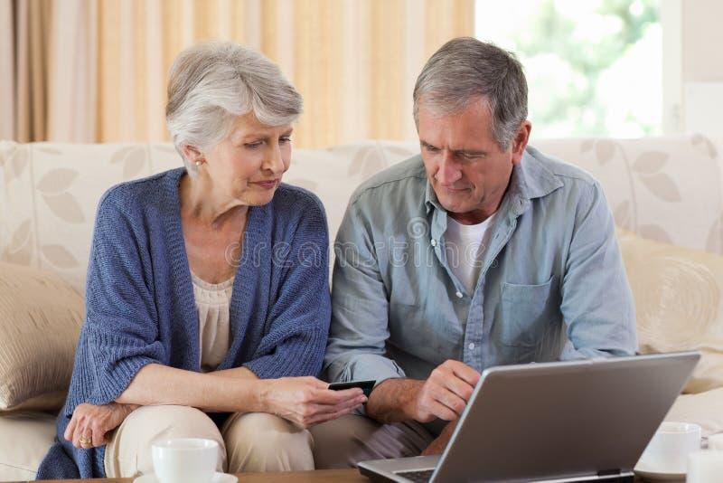 Pares aposentados que olham seu portátil fotos de stock