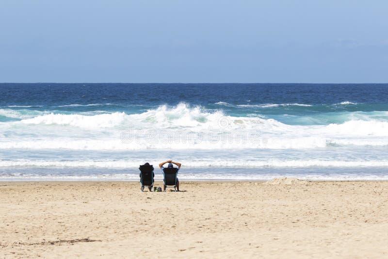 Pares aposentados que sentam-se na praia foto de stock royalty free