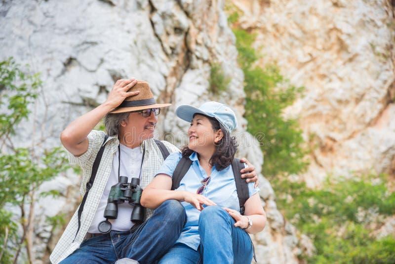 Pares aposentados que sentam-se no monte e no sorriso fotos de stock royalty free