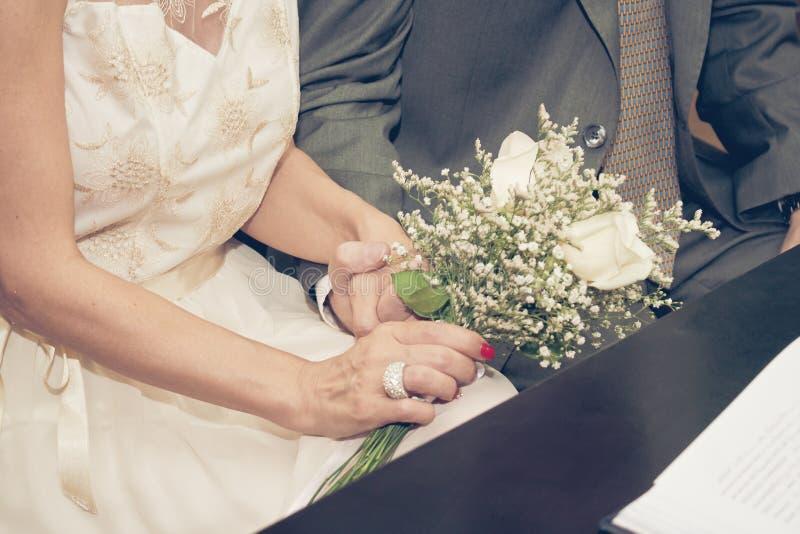 Pares aproximadamente para casar-se guardar as mãos com um ramalhete da flor foto de stock
