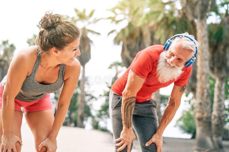 Pares aptos de los amigos que tienen una rotura después de una raza rápida después la playa en la puesta del sol - entrenamiento  imagen de archivo libre de regalías