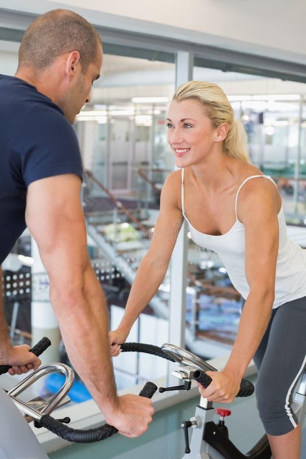 Pares aptos de sorriso que trabalham em bicicletas de exercício no gym imagem de stock