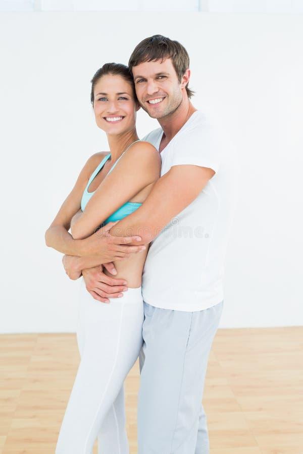 Pares aptos que abraçam no estúdio da aptidão fotografia de stock royalty free