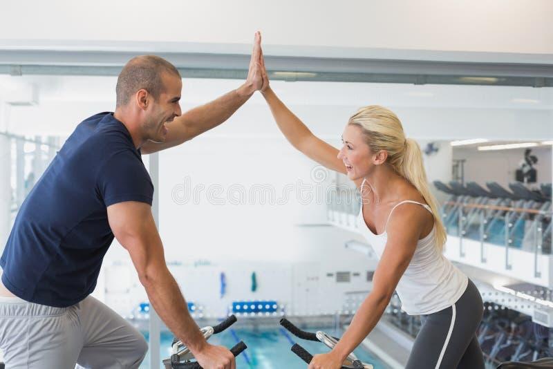 Pares aptos que dão a elevação cinco ao trabalhar em bicicletas de exercício no gym foto de stock royalty free